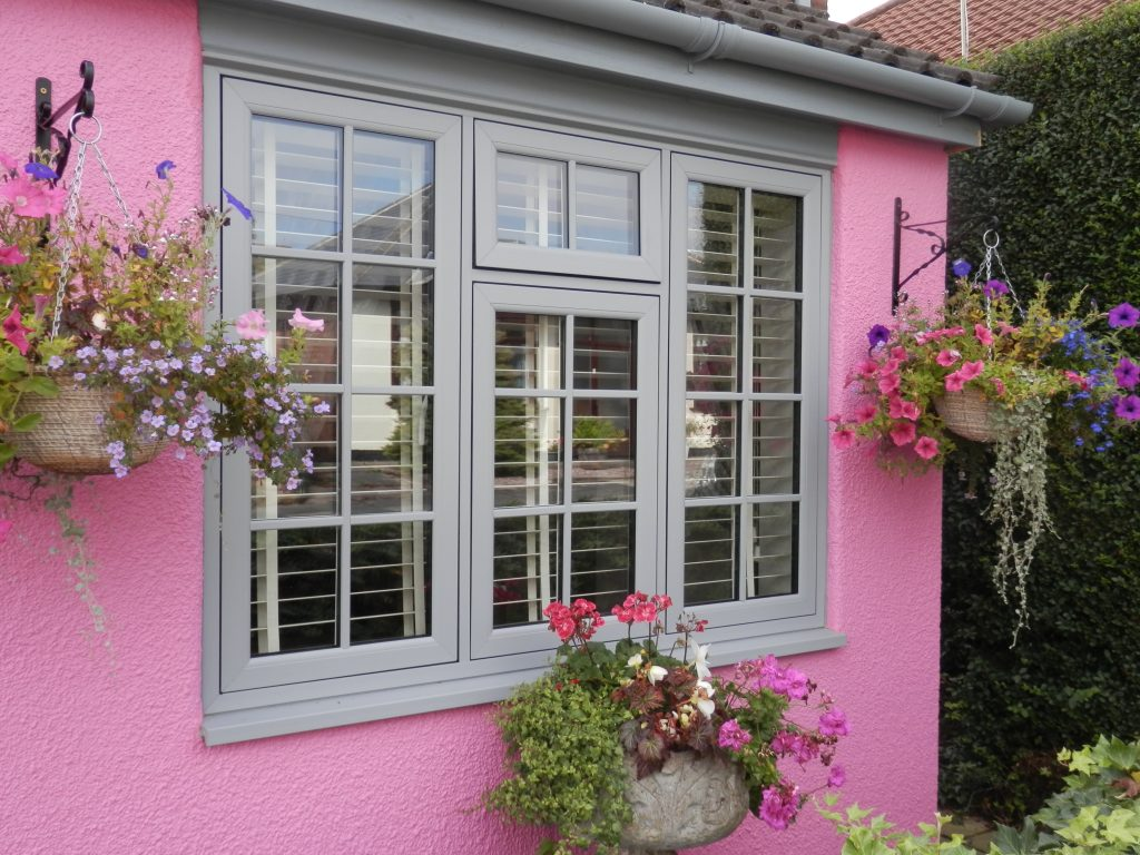 flush sash windows set in a pink house wall