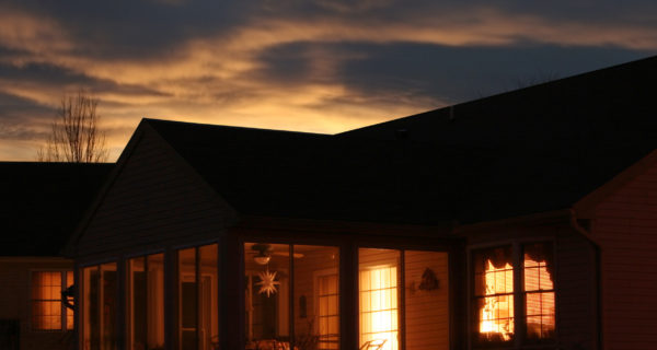 Looking into a house as the sun goes down. Lights inside duplicate sky lights behind. Warm glow of home.