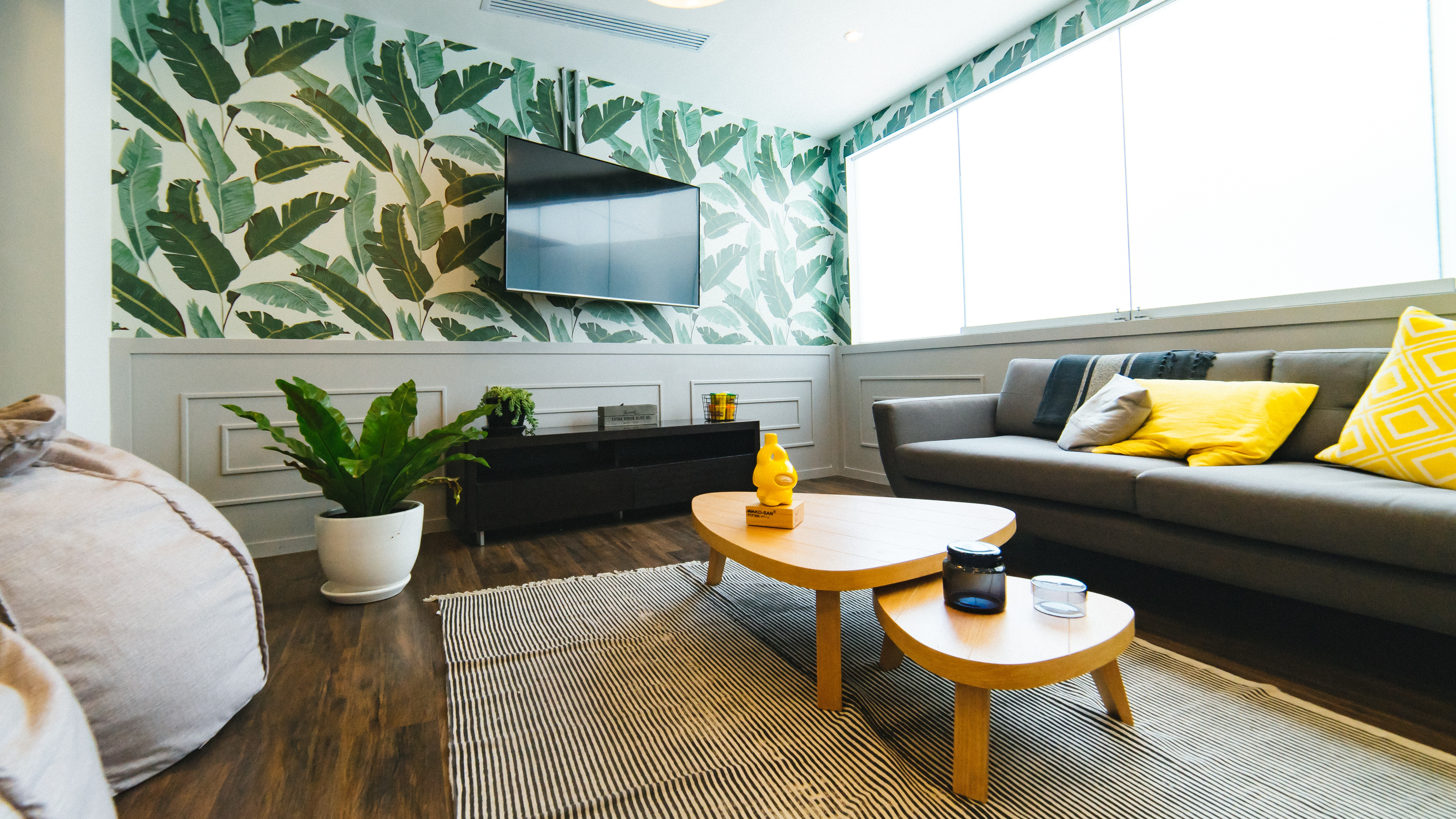 tropical home interior with house plants, bright colours and natural patterned wallpaper