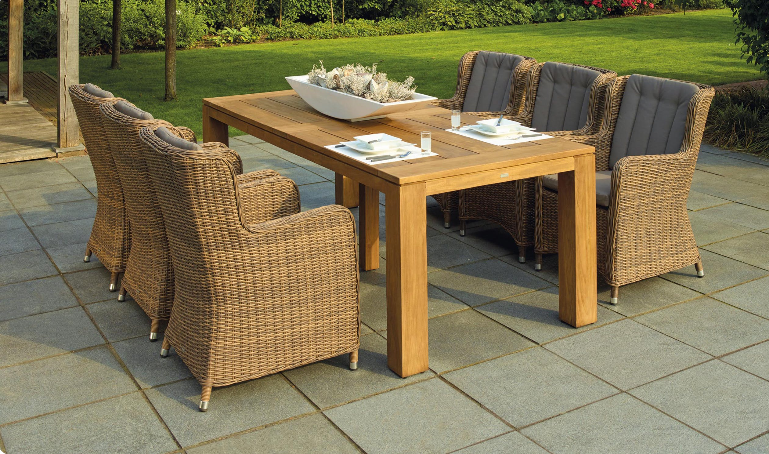 wooden garden table with six wicker chairs.