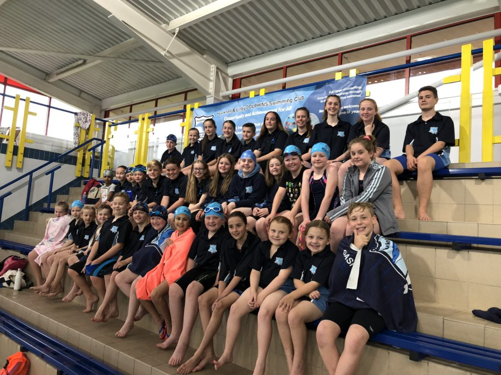 Young swimmers from the Hucknall and Linby Dolphins sit in tired seating by the pool to have a club photo.
