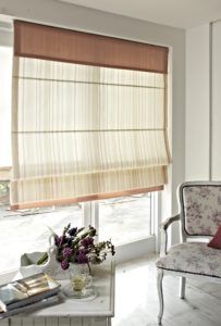 Roman blinds drawn halfway up a window.