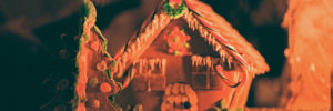 Beautiful gingerbread house with Christmas tree in orange lighting, showing creativity with candy cane roof.